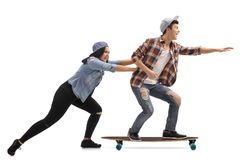 Teenage girl pushing a teenage boy on a longboard. Full length profile shot of a teenage girl pushing a teenage boy on a longboard isolated on white background stock image