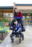 Teenage girl pushing disabled boy in wheelchair. Teenage girl pushing her little disabled brother in wheelchair leaving school royalty free stock images