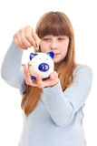 Teenage girl putting coin in piggy bank Royalty Free Stock Photos