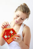 teenage girl putting coins in her moneybox Stock Photography