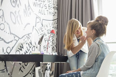 Teenage girl putting lipstick on sister at home Royalty Free Stock Photos