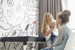 Teenage girl putting lipstick on sister at home Royalty Free Stock Image