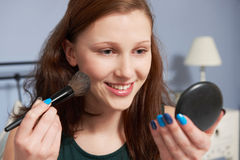 Teenage Girl Putting On Make Up In Mirror stock photography
