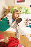 Teenage Girl Putting On Make Up In Untidy Bedroom Stock Images