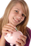 Teenage girl putting money piggy bank savings. Teenage girl smiles while she is saving her money by putting it into a pink piggy bank she is holding in front of Stock Photos