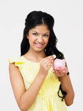 Teenage Girl Putting Money Into Piggy Bank Royalty Free Stock Image