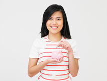 Teenage Girl Putting Money Into Piggy Bank Stock Photo