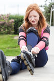 Teenage girl putting on rollerblades Stock Photo