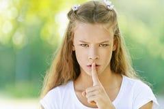 Teenage girl raised index finger. Beautiful teenage girl in white blouse raised index finger to her lips, against green of summer park stock image
