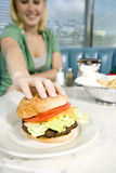 Teenage girl reaching for a hamburger in a diner Stock Photos
