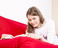 Teenage girl readin on a couch Stock Images