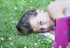 Teenage girl readin on tablet stock images