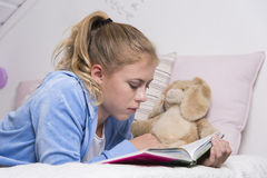 Teenage girl reading on a bed Stock Images