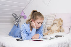 Teenage girl reading on a bed Royalty Free Stock Photos