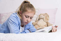 Teenage girl reading on a bed Royalty Free Stock Images