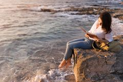 Be free, work whenever you want. Teenage girl reading book on the beach in sunset royalty free stock photos
