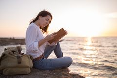 Be free, work whenever you want. Teenage girl reading book on the beach in sunset stock images