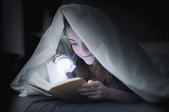 Teenage girl reading a book in bed under the covers Royalty Free Stock Photos