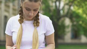 Teenage girl reading book outdoors, remembering information, preparing for exam stock video