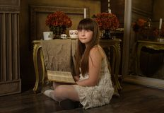Teenage girl is reading a book in a room. NPhotoshoot in the studio in the style of a fairytale photo.nVintage photo shoot stock photography