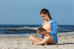 Teenage girl reading book sitting on beach Royalty Free Stock Images
