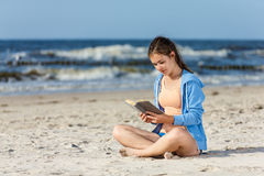 Teenage girl reading book sitting on beach Stock Images