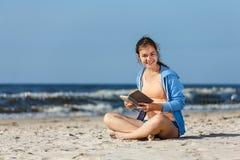 Teenage girl reading book sitting on beach Royalty Free Stock Image