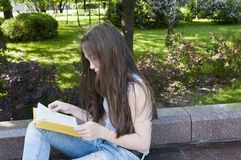 Cute teenage girl reading book sitting on the bench in park, studying outdoor. Stock Photo