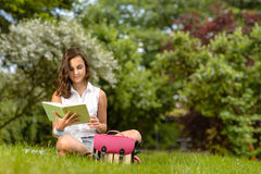 Teenage girl reading book sitting in park Royalty Free Stock Images