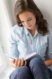 Teenage girl reading book sitting by window Royalty Free Stock Photography