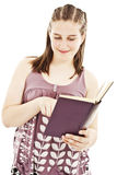 Teenage Girl Reading a Book and Smiling Royalty Free Stock Image