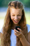 Teenage girl reading funny message Royalty Free Stock Photography