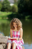 Teenage girl reading by the lake Stock Photo