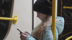 Teenage girl reading from mobile phone screen in metro. Teenage girl reading from mobile phone screen in metro stock footage