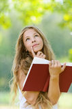 Teenage girl reading red book Stock Image