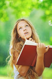 Teenage girl reading red book Stock Images