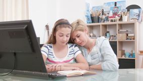 Teenage girl reading to her mom from a book stock footage