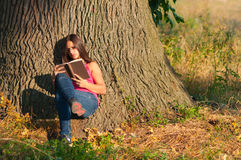 Teenage girl reads the book under the oak tree Stock Photography