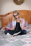 A teenage girl reads while listening to music. Stock Photos