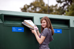 A teenage girl recycling magazines Royalty Free Stock Image