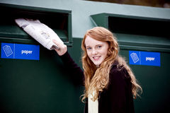 A teenage girl recycling newspapers Stock Image