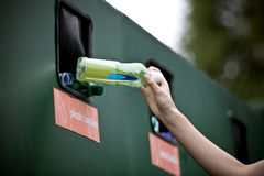 A teenage girl recycling a plastic bottle Stock Images