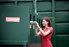 A teenage girl recycling a plastic bottle Royalty Free Stock Photography