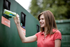 A teenage girl recycling a plastic bottle, smiling Stock Image