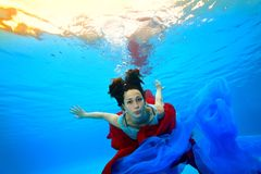 A teenage girl with a red and blue cloth dives underwater on the bottom of the pool against the background of bright lights. And looks at the camera. Portrait Stock Photos