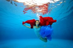 A teenage girl with a red and blue cloth in her hands swims and poses underwater near the bottom and looks at the camera. Portrait. Shooting under water Royalty Free Stock Photography