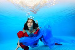 A teenage girl with a red and blue cloth swims underwater near the bottom and looks at the camera. Portrait. Shooting under water. Horizontal orientation Royalty Free Stock Images