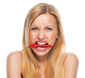 Teenage girl with red chili pepper in mouth Stock Photography