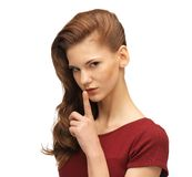 Teenage girl in red dress with finger on lips Royalty Free Stock Images