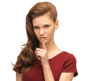 Teenage girl in red dress with finger on lips Royalty Free Stock Photos